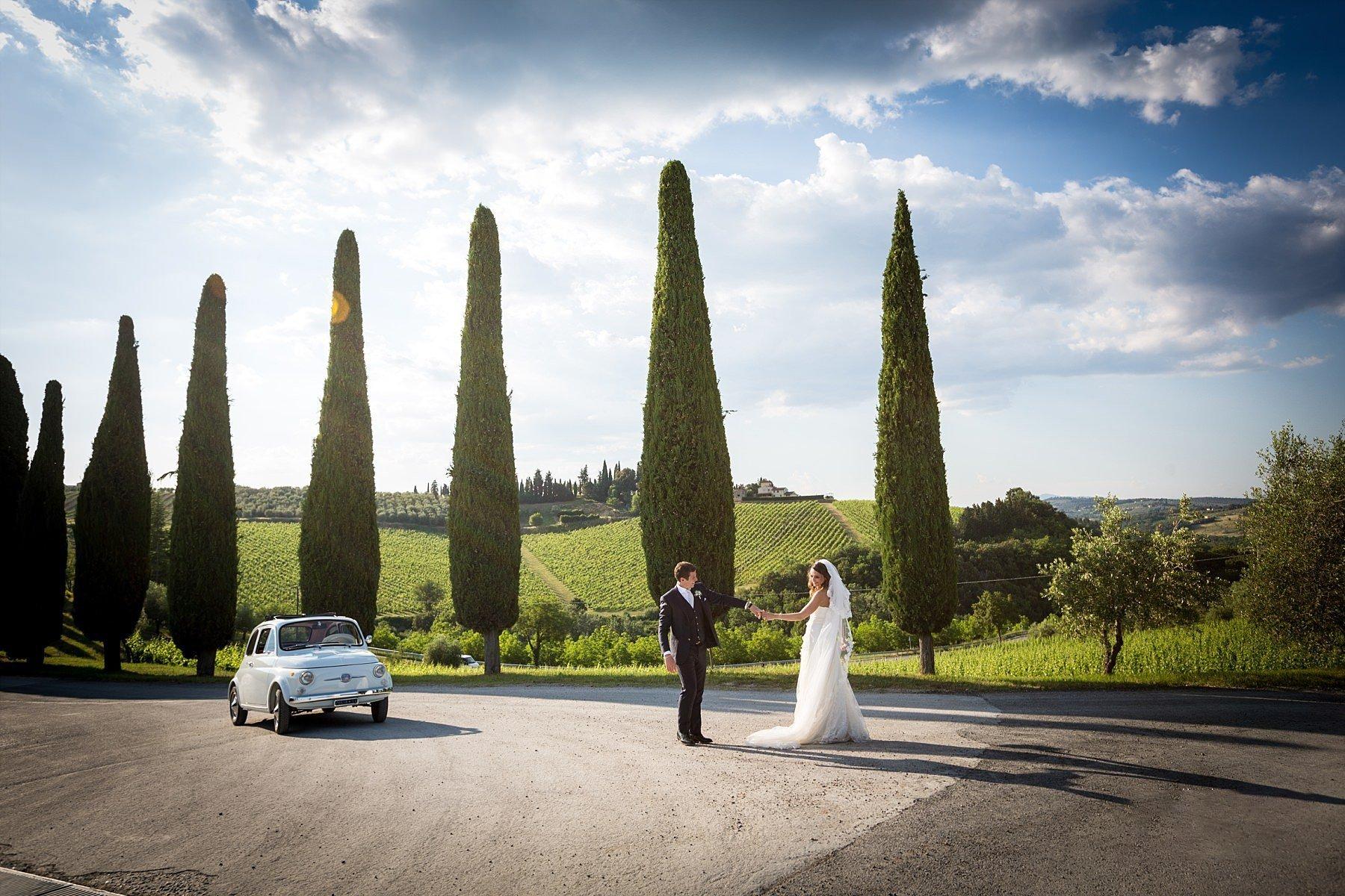 Sposi con fiat 500 fotografati nelle bellissime colline toscane con cipressi
