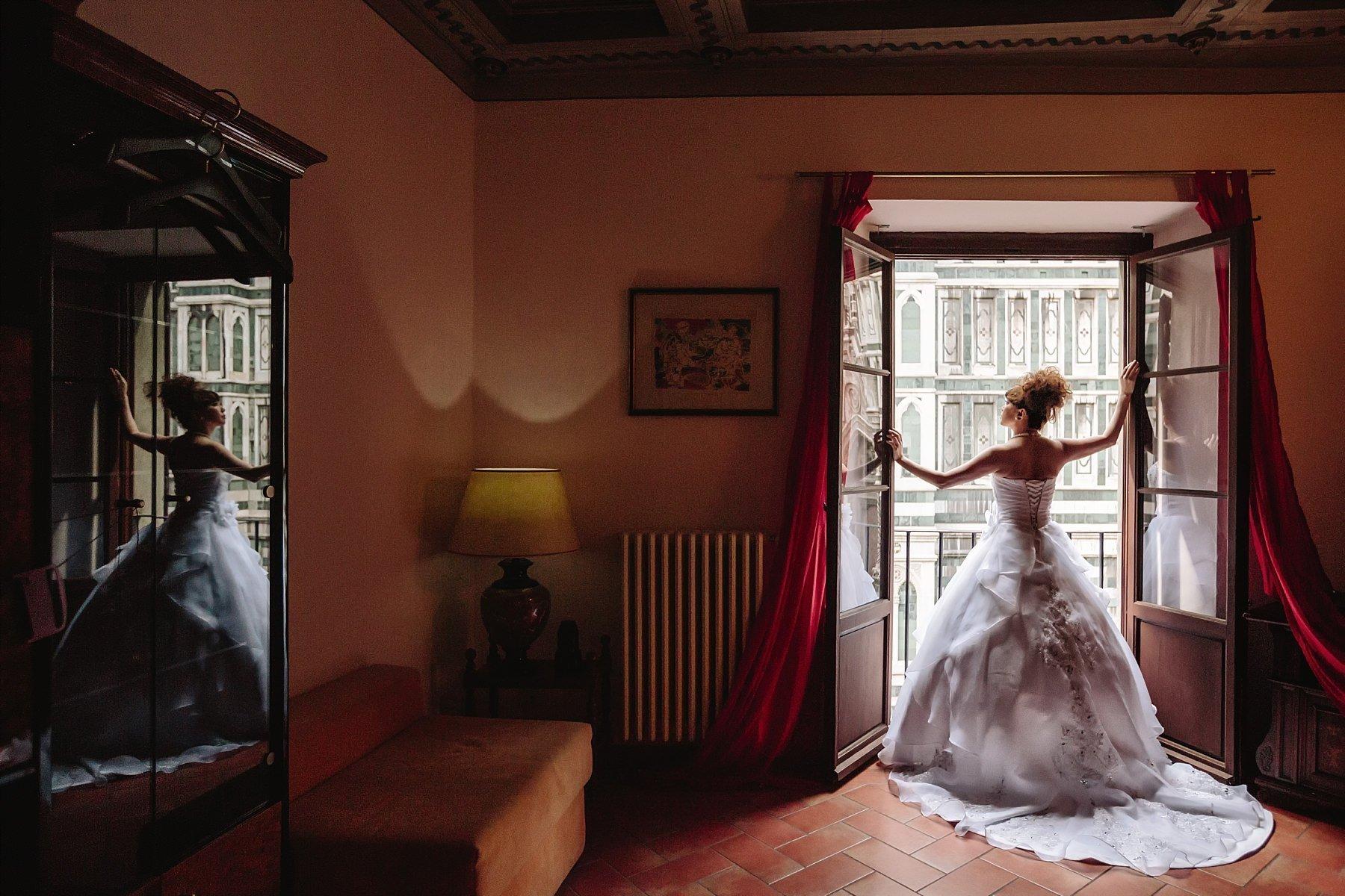 Foto da dietro di una sposa giapponese con un bellissimo abito che si affacciada una finestra con vista duomo di firenze