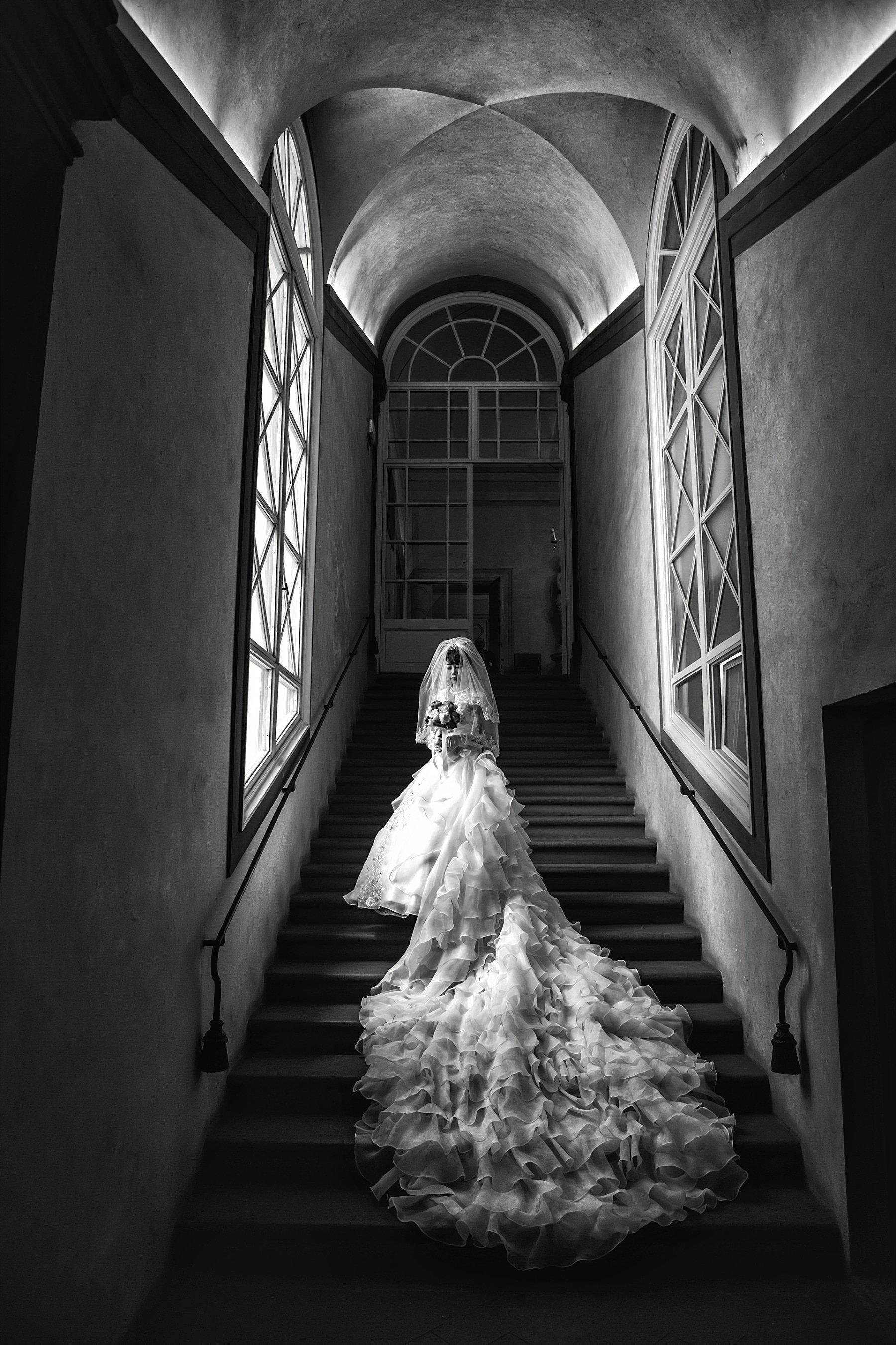 Foto in Bianco e Nero di una Sposa con un lunghissimo abito sulla scalinata del Palazzo Veccio a Firenze