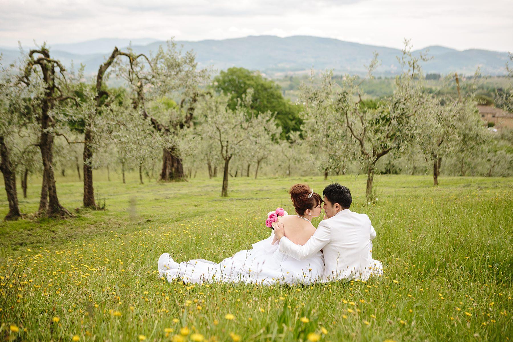 Fotografia di matrimonio con sposi seduti sul prato