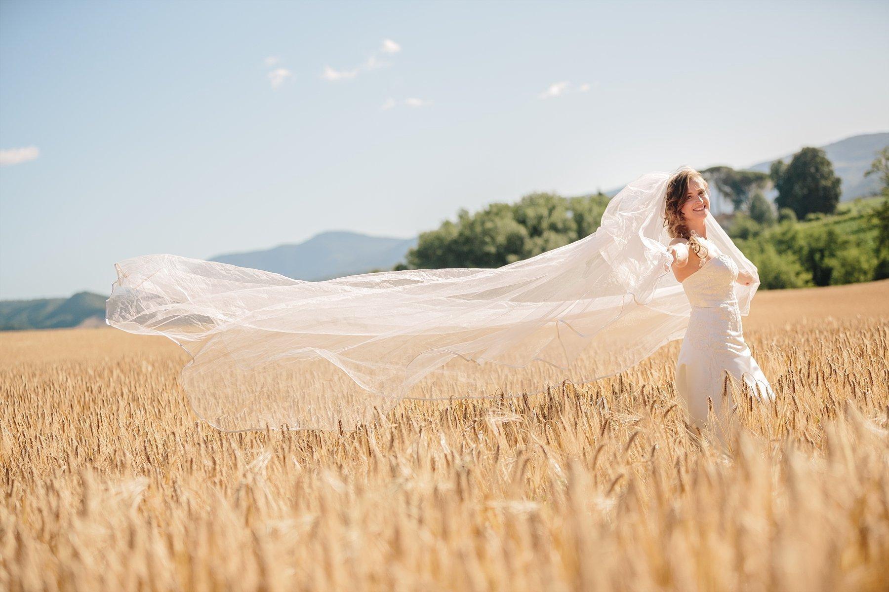 Sposa con velo in un campo di grano nel Mugello