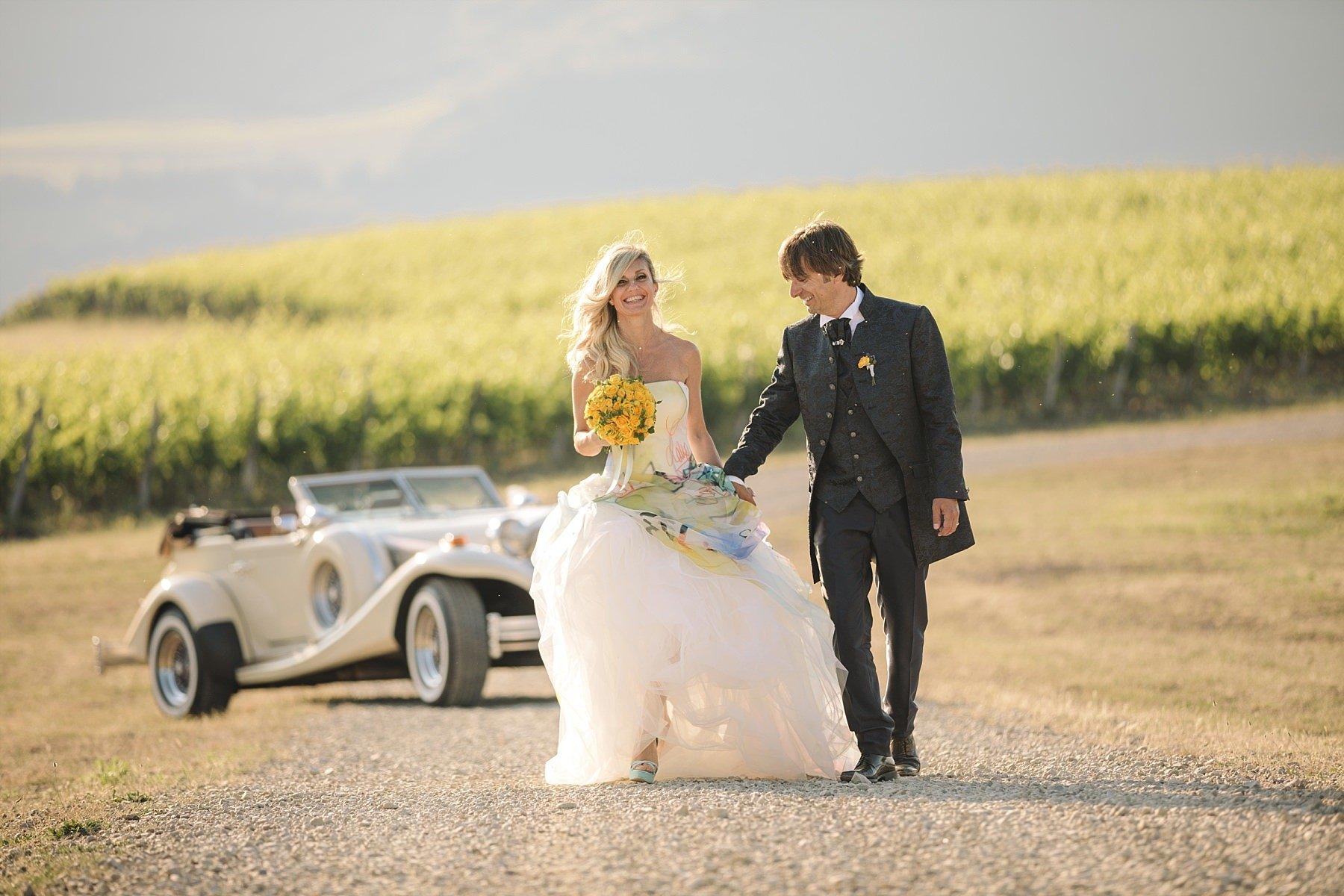 Reportage di sposi che camminano nelle vigne in toscana con la macchina in sfondo