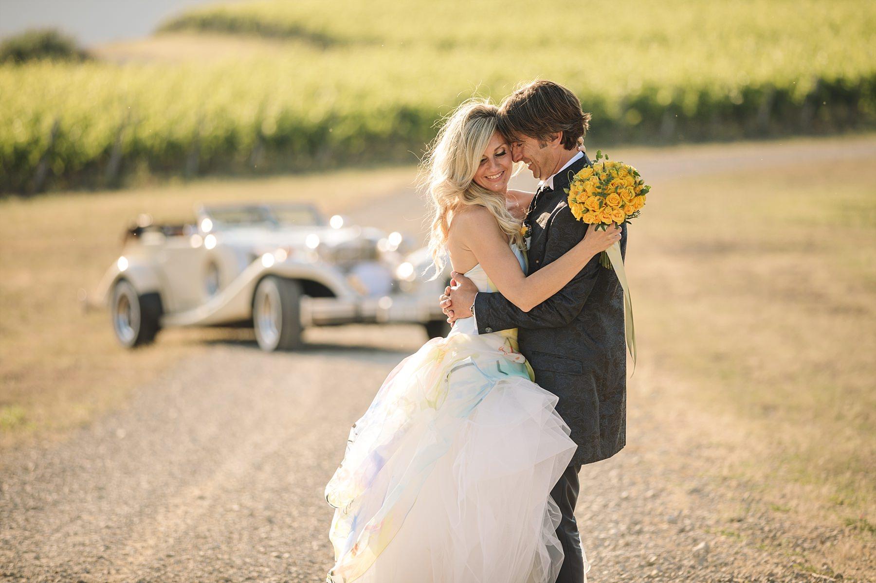 Reportage di sposi nelle vigne in toscana con la macchina in sfondo