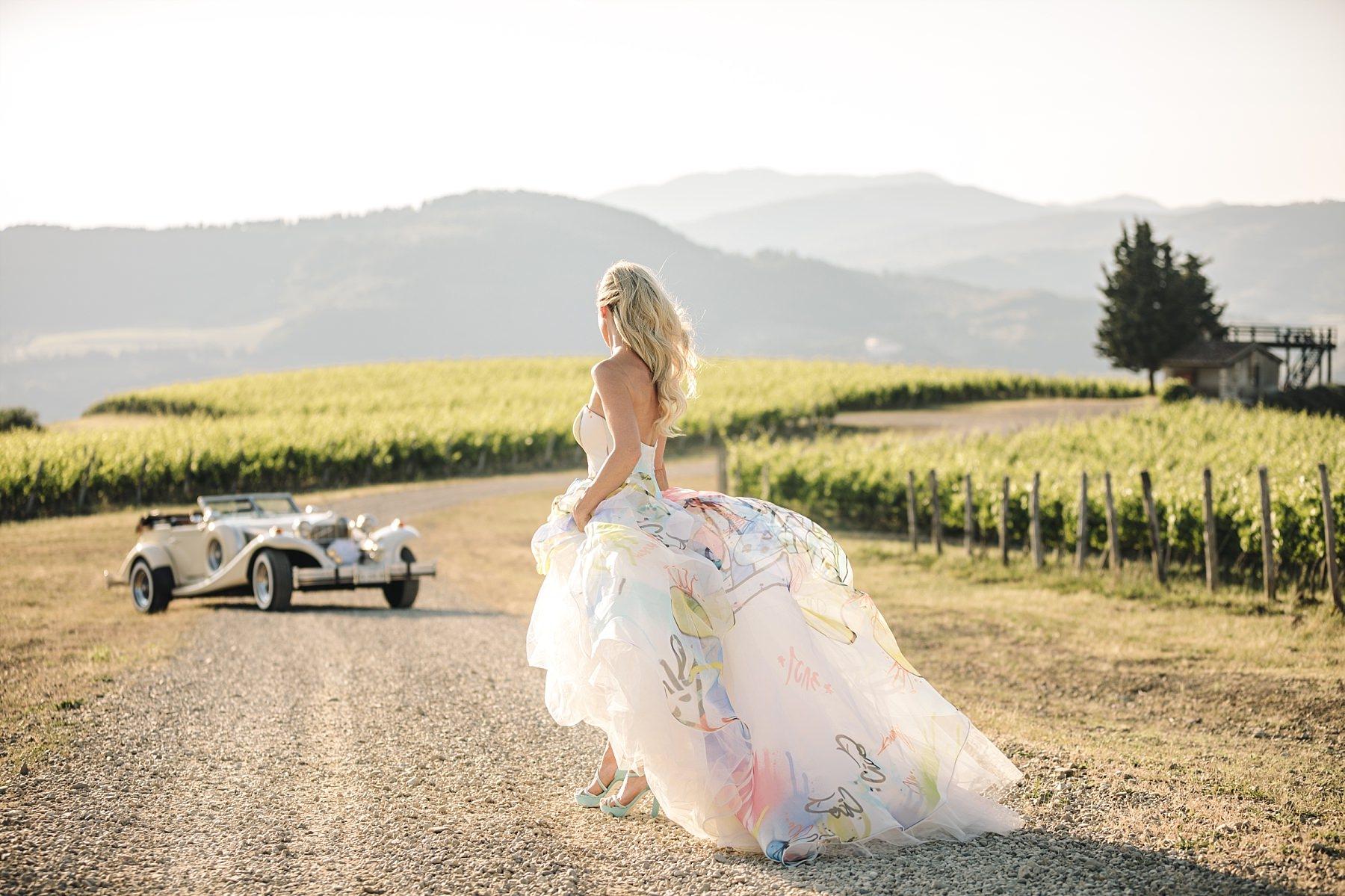 Bellissimo abito Atelier Emé ritratto da dietro indossato da una sposa nelle vigne in toscana