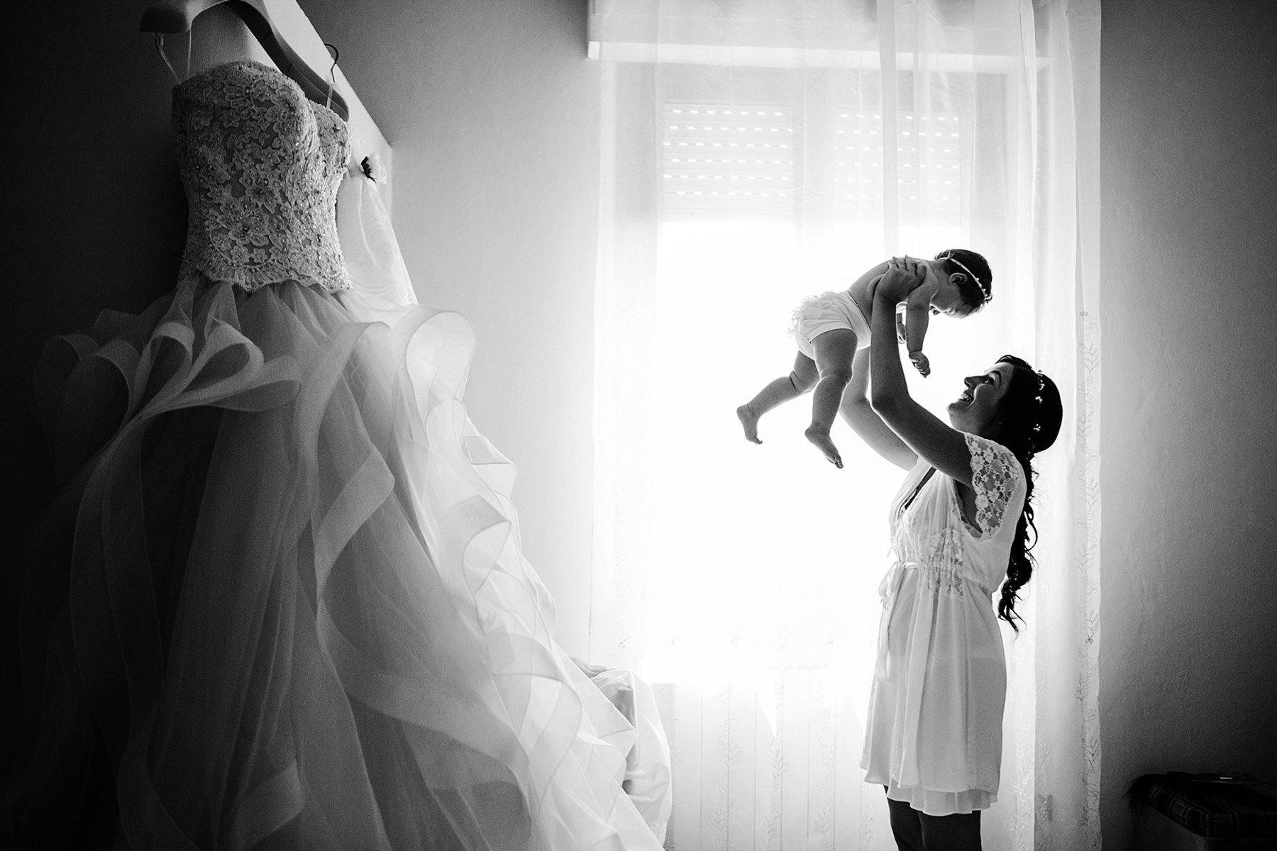 sposa che si prepara con sua figlia in braccio