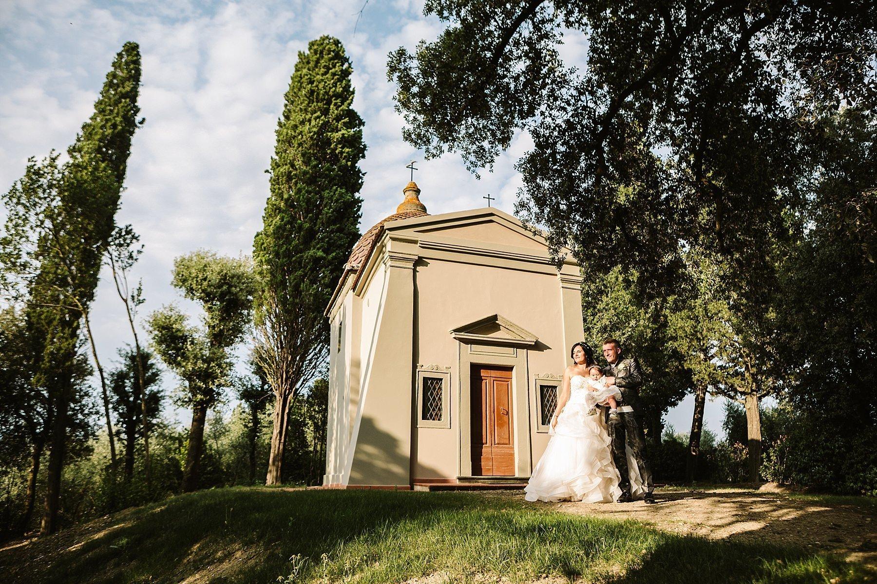 coppia di sposi con la loro figlia in braccio davanti ad una chiesa
