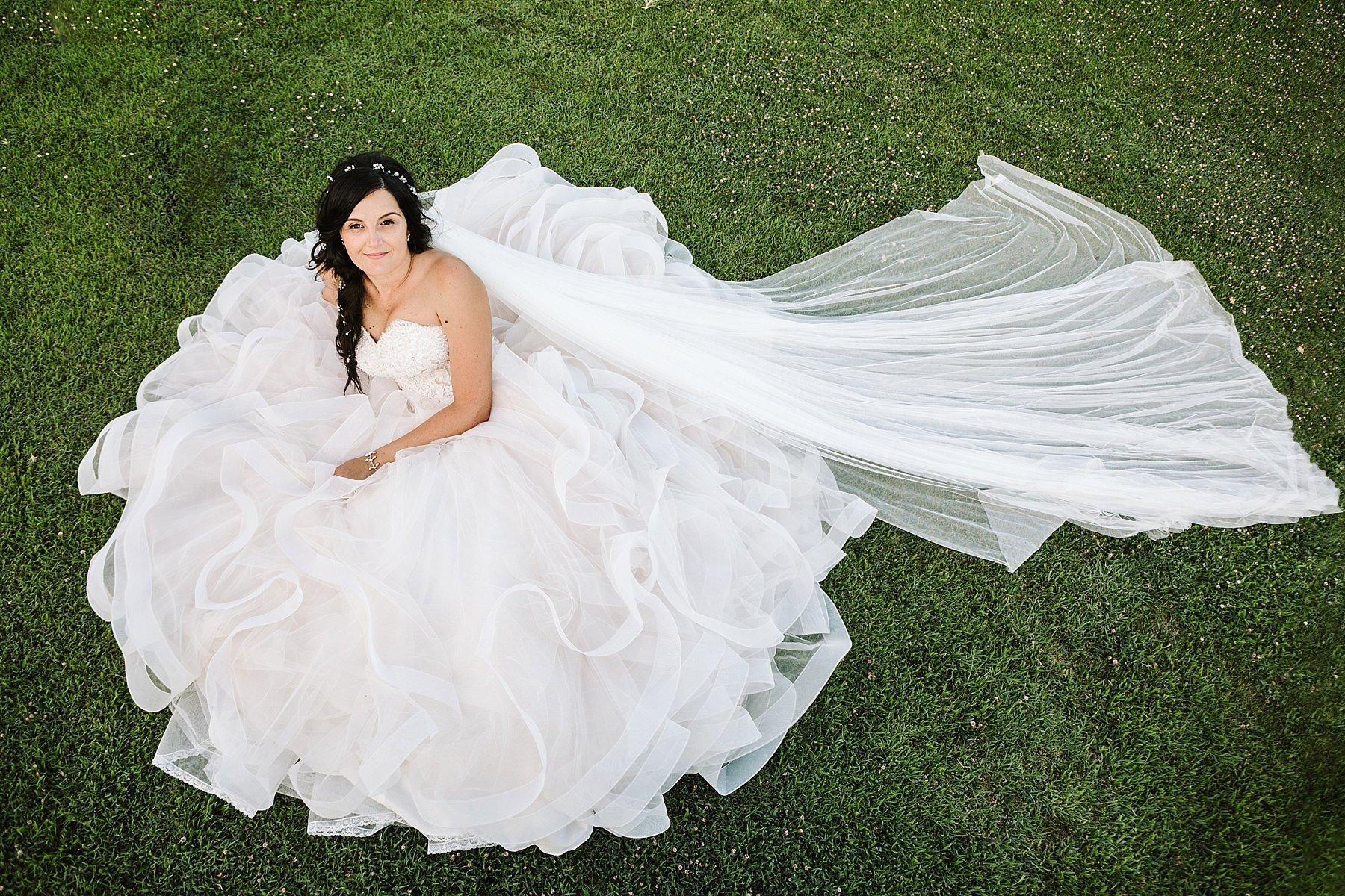 sposa seduta sul prato con un grandissimo vestito