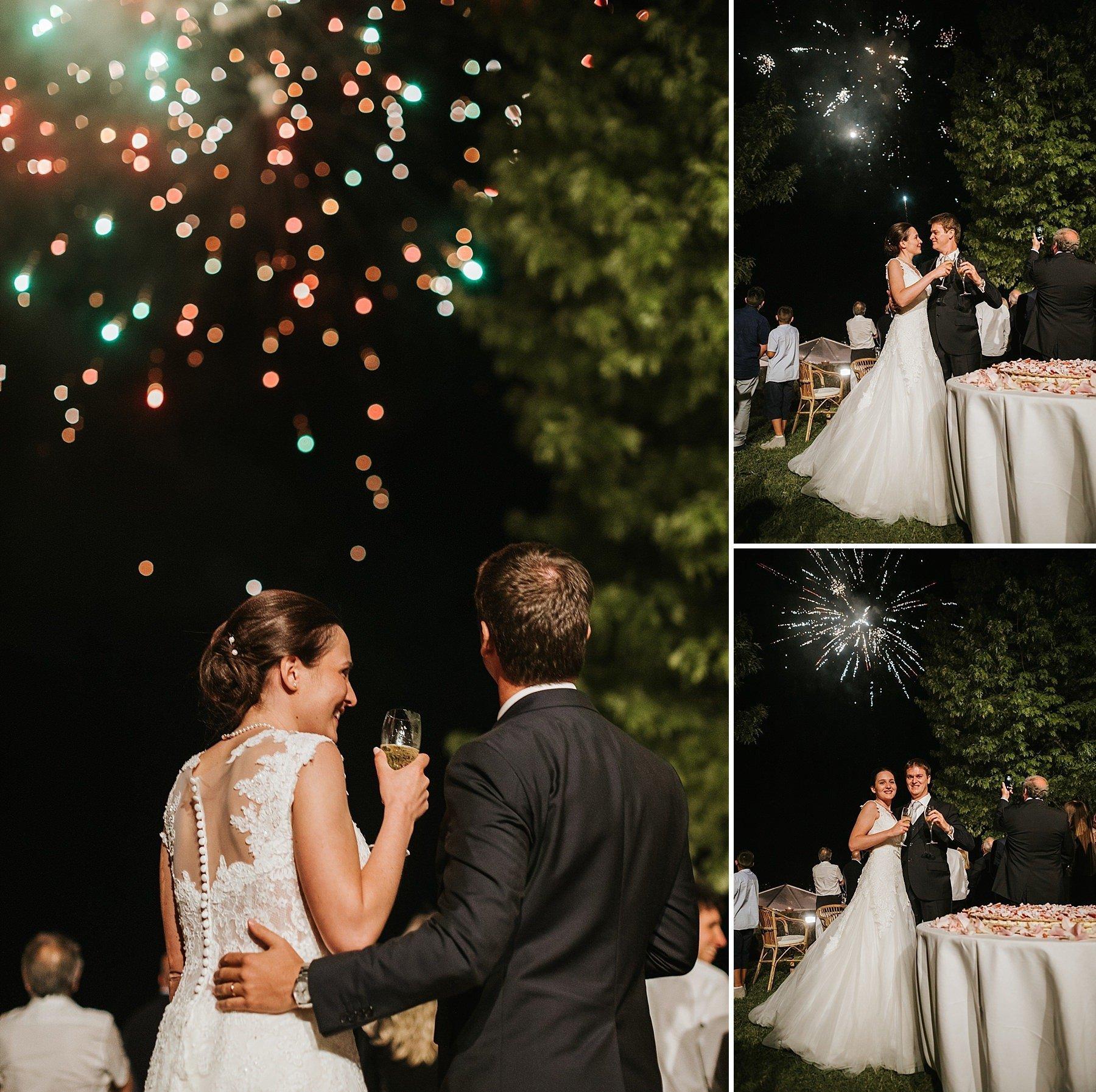 Sposo e sposa mentre brindano con i fuochi d'artificio