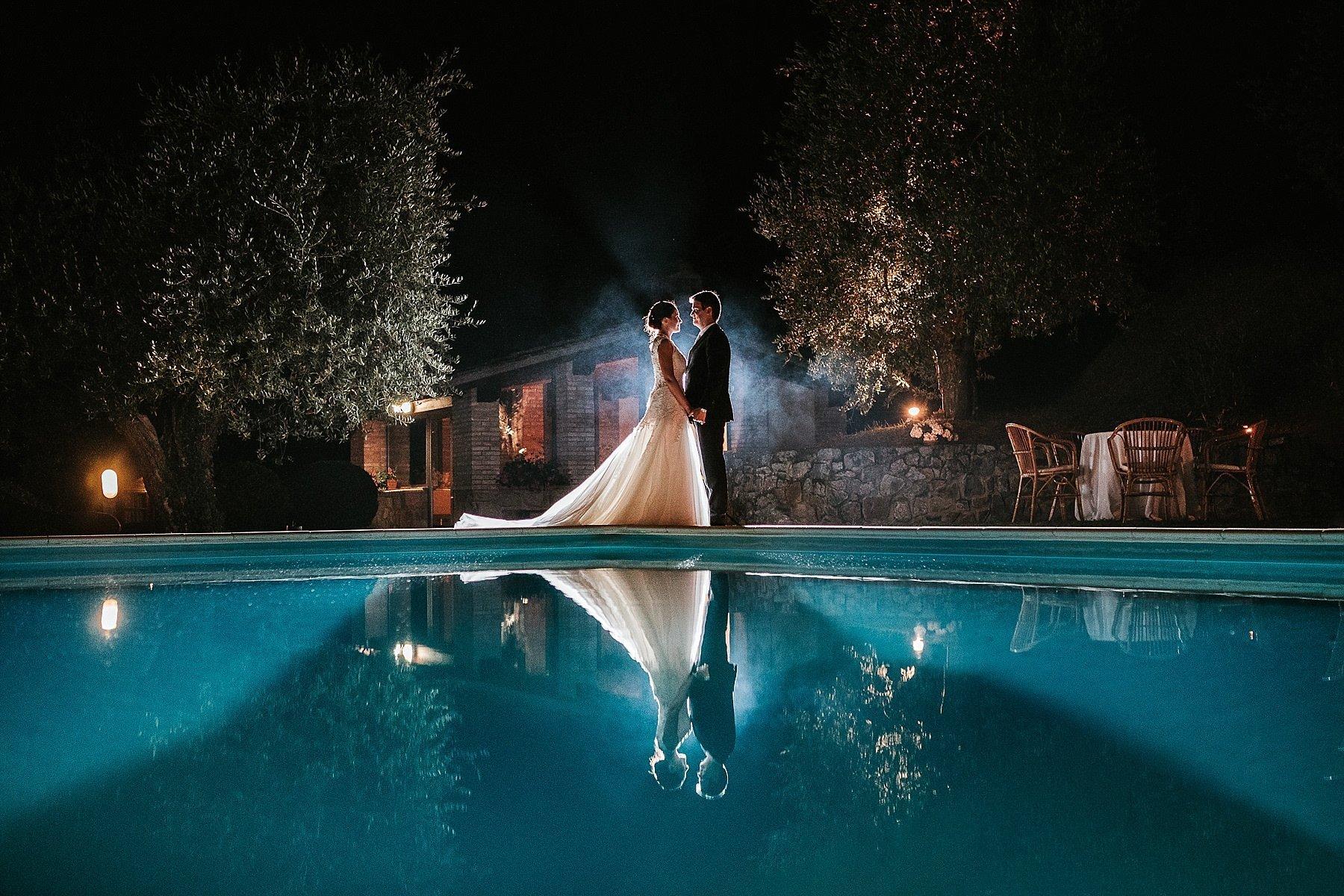 Spettacolare fotografia di matrimonio con sposi a bordo piscina di notte
