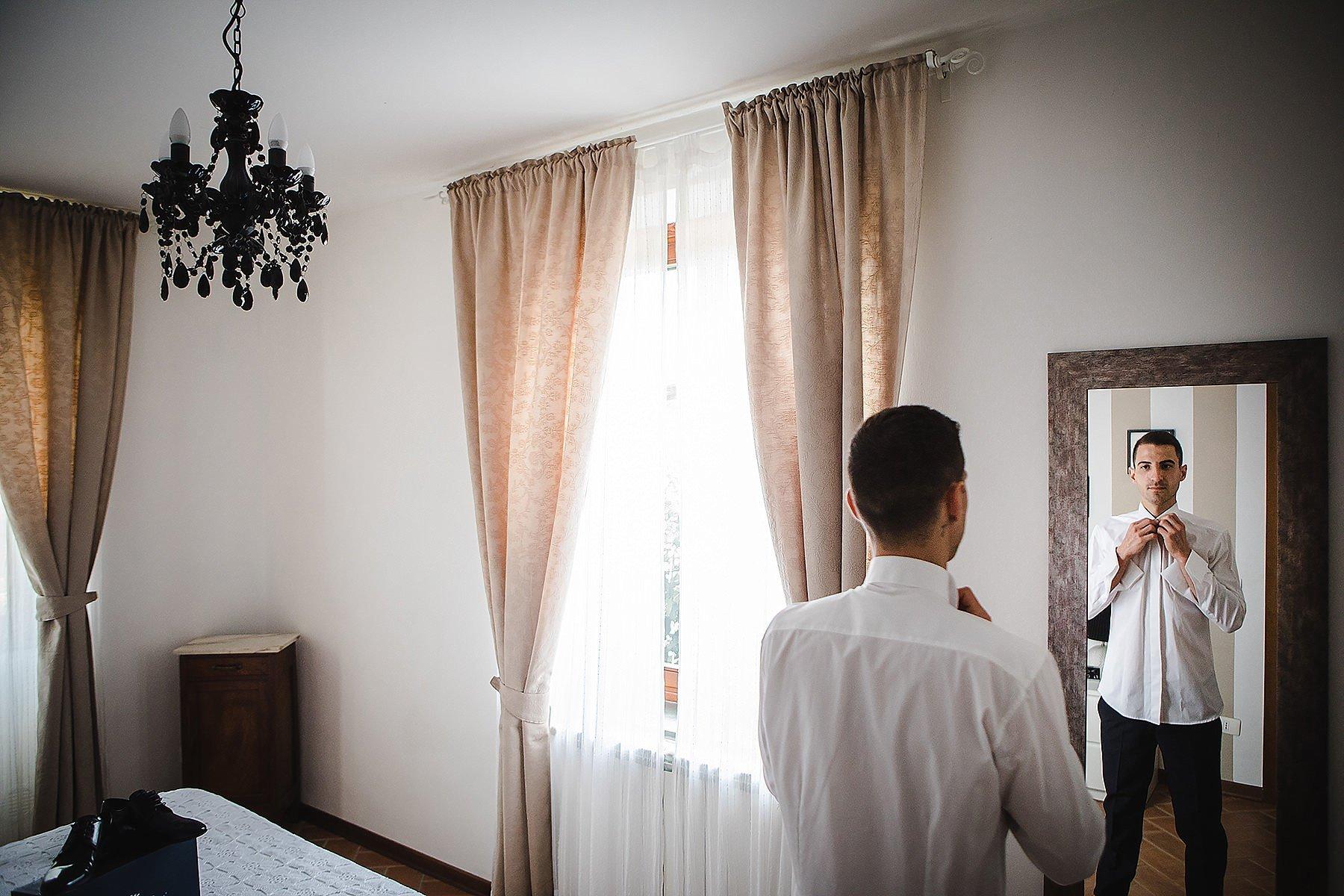 sposo che si guarda allo specchio mentre si prepara