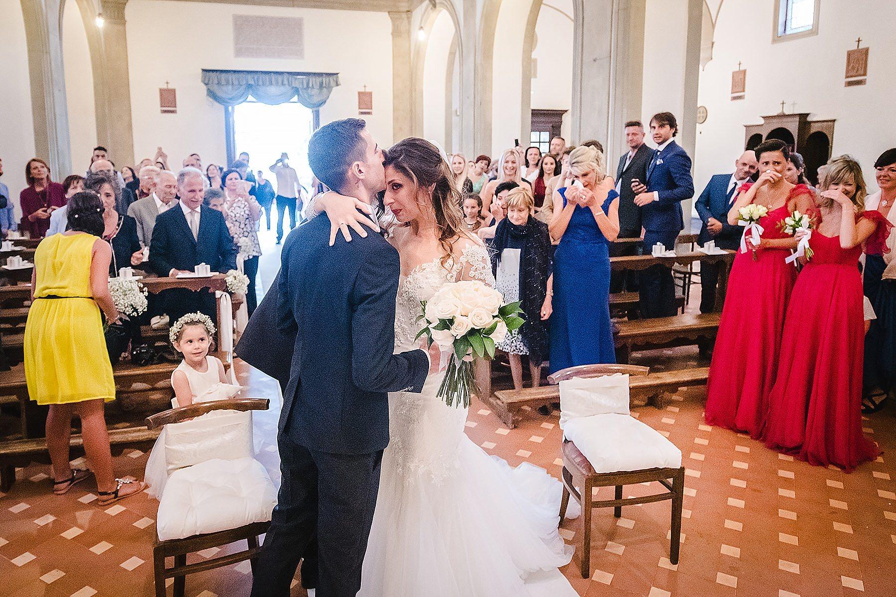 sposo che bacia la sposa dopo il suo ingresso in chiesa