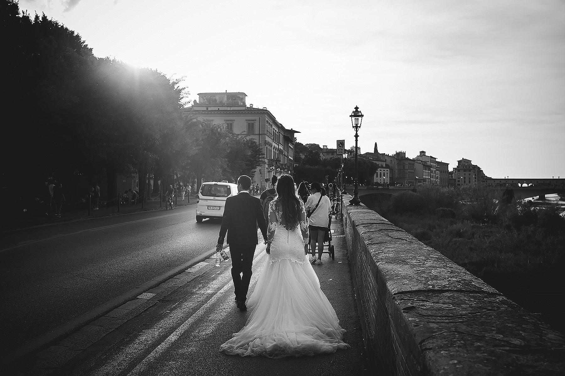foto artistica in bianco e nero di sposi mantre camminano a Firenze sui lungarni