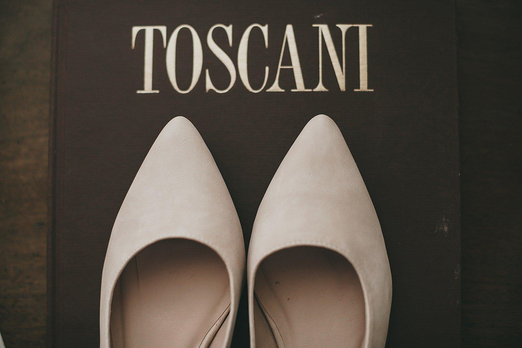 Scarpe da sposa fotografate su un libro con scritto Toscani