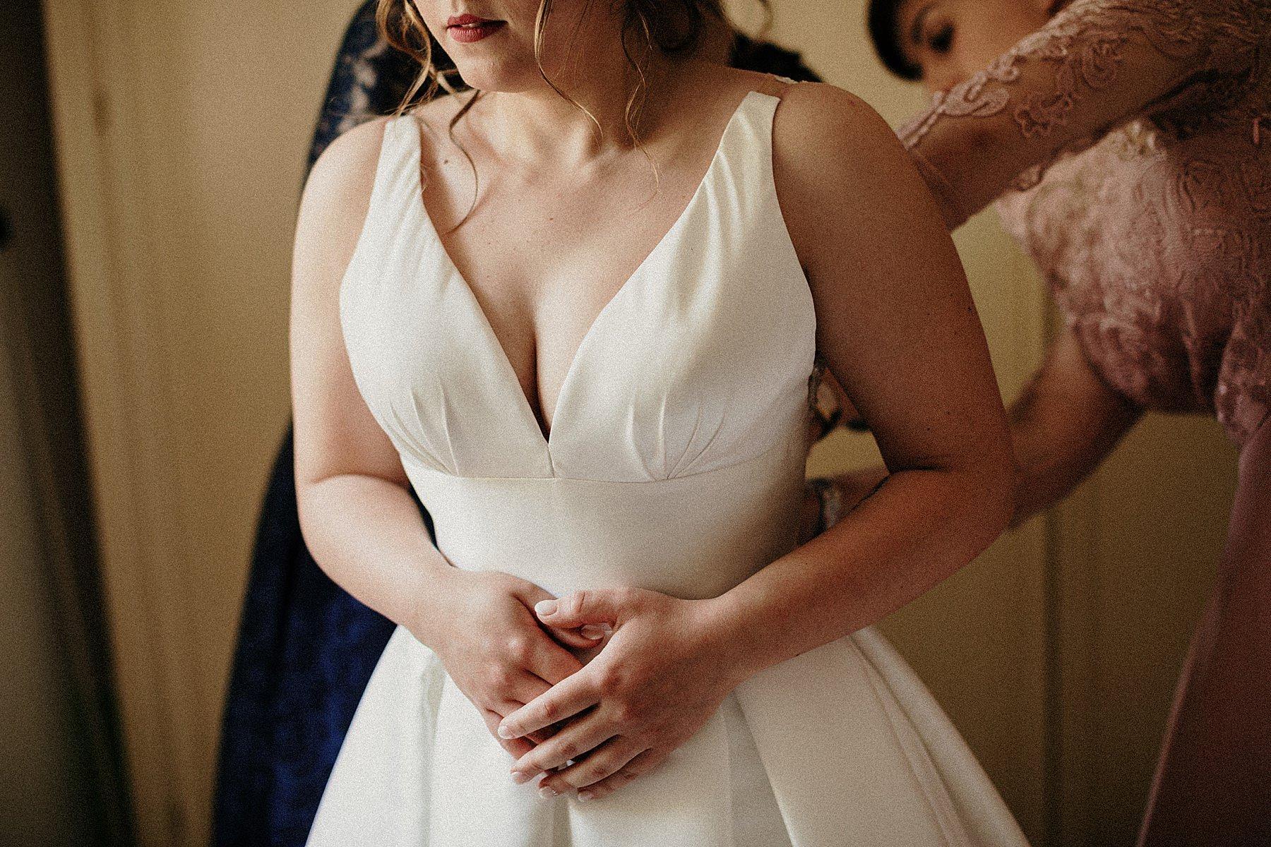 Sposa mentre si mette il vestito