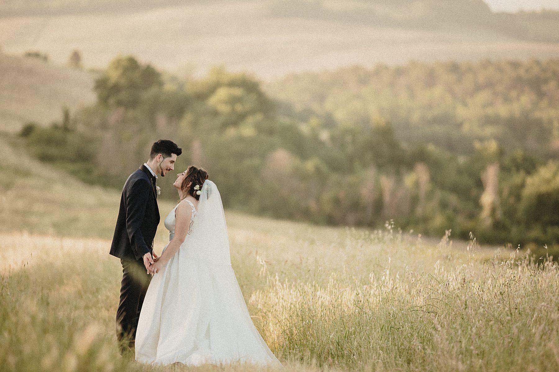 Foto romantica di sposi nel paesaggio toscano