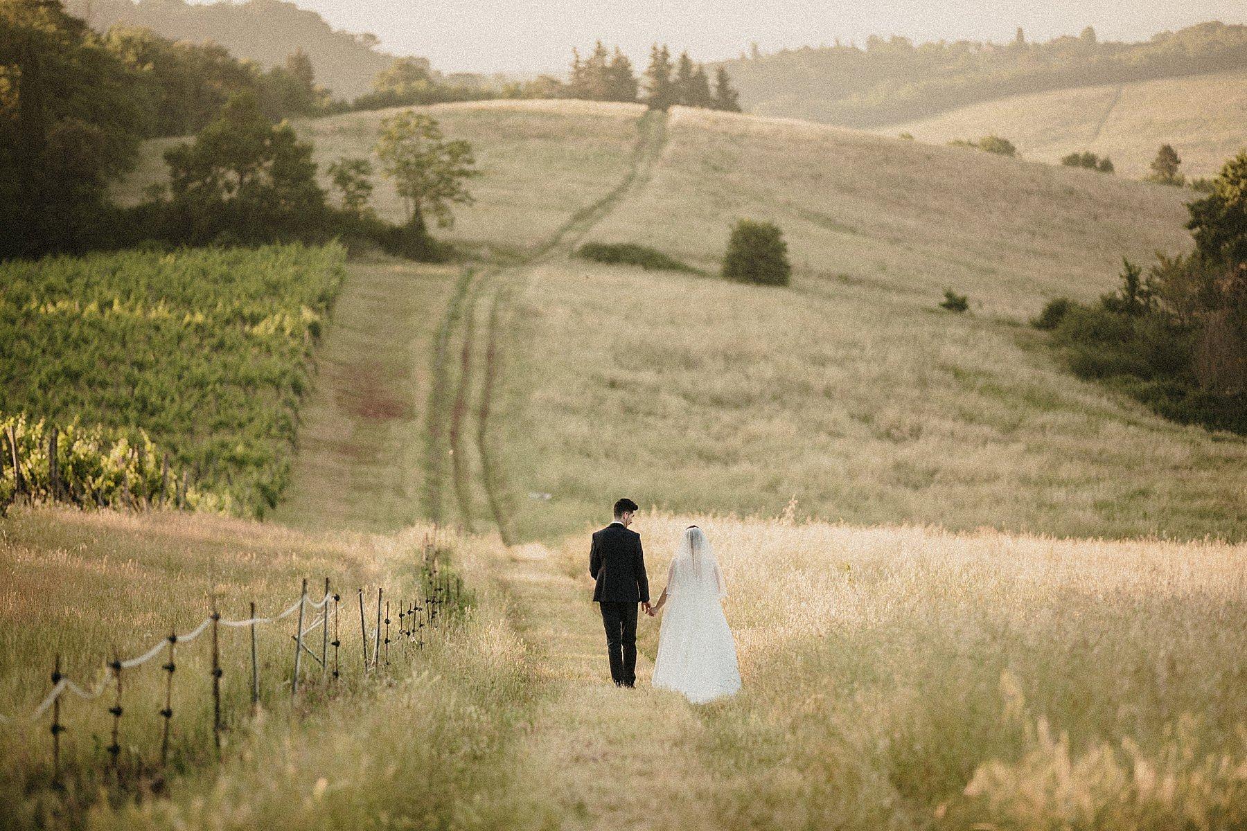 sposi che camminano in un bellissimo campo tra le colline toscane