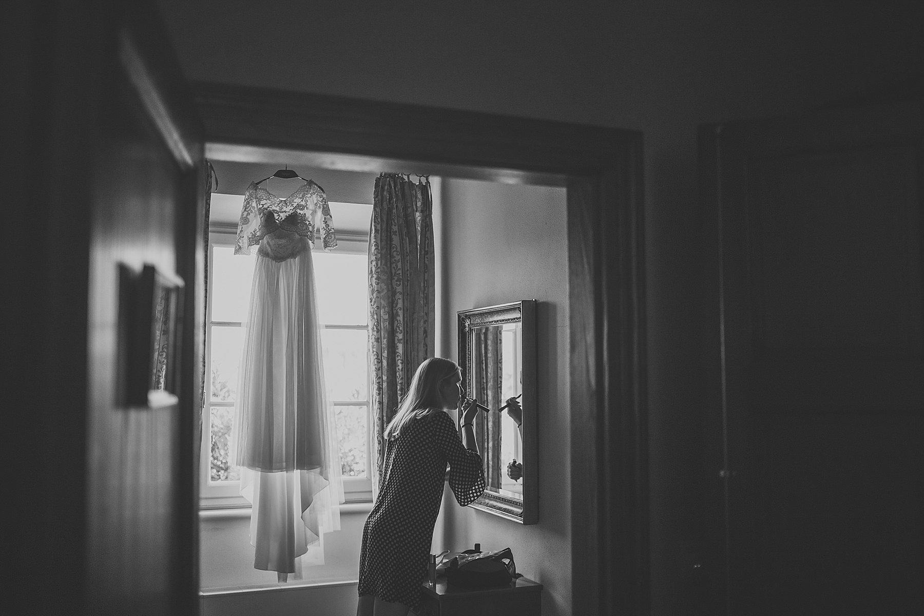 Amica della sposa che si trucca davanti allo specchio