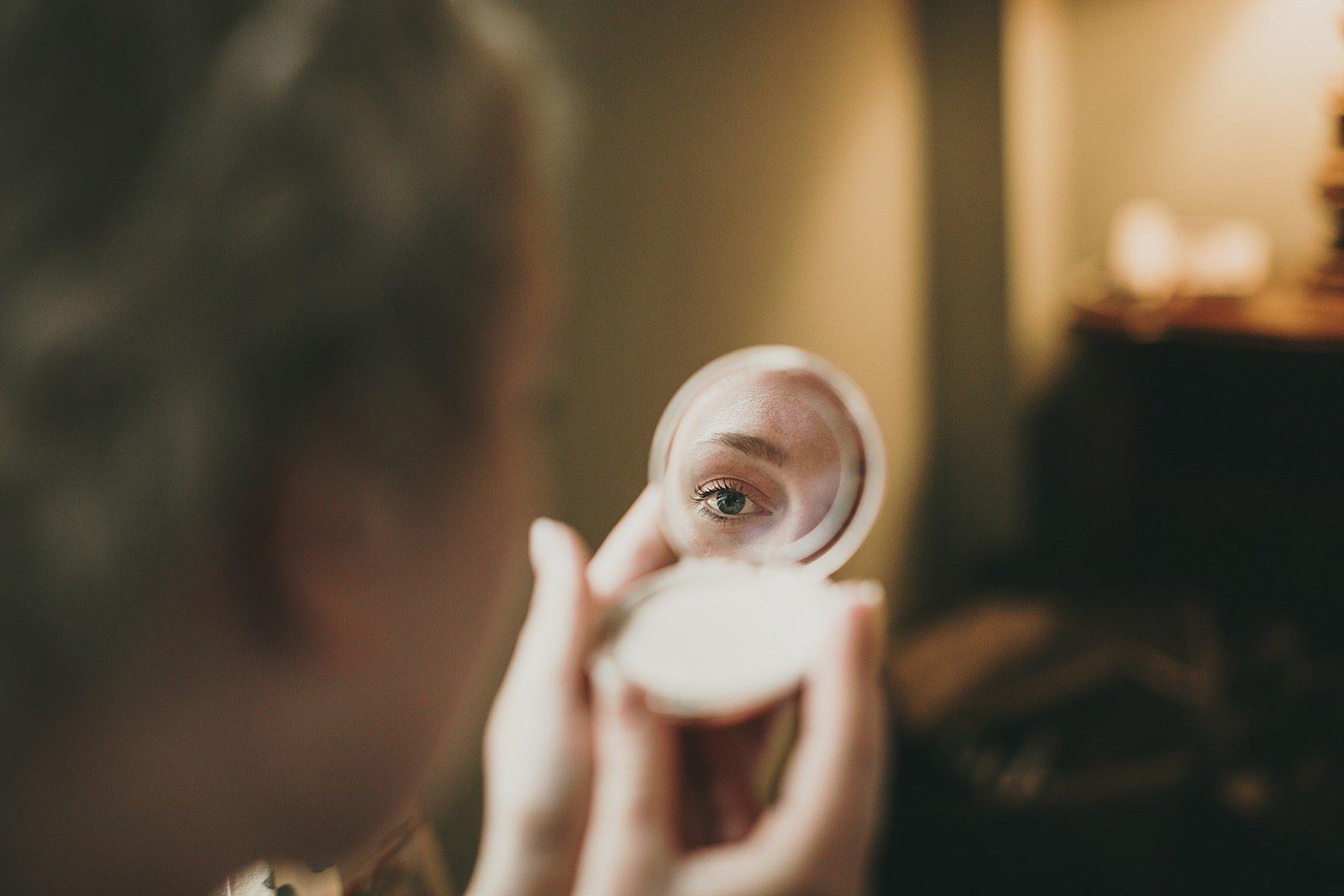 Sposa che su trucca e si guarda allo specchio
