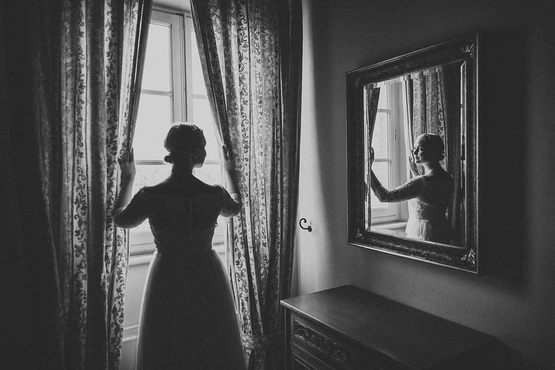 Sposa affacciata alla finestra riflessa nello specchio